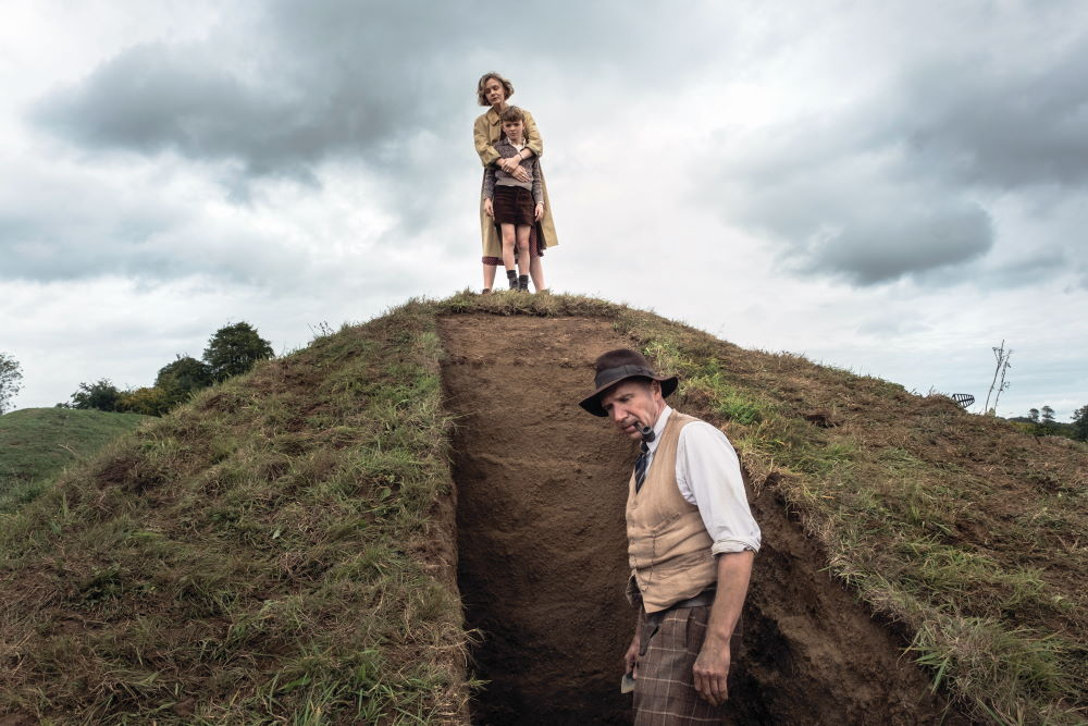 Ralph Fiennes as Basil Brown, Carey Mulligan as Edith Pretty, and Archie Barnes as her son Robert, at the recreated Sutton Hoo mound in The Dig.