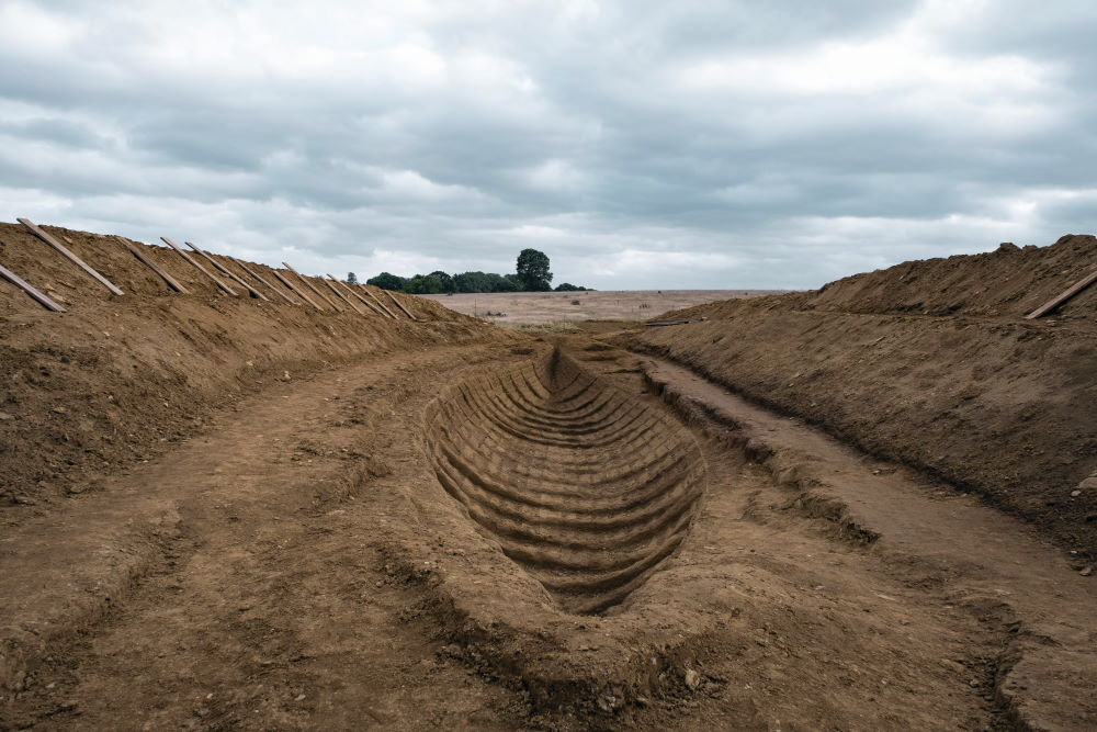 A recreation of the Sutton Hoo excavation and the imprint of the ship as it appears in The Dig.